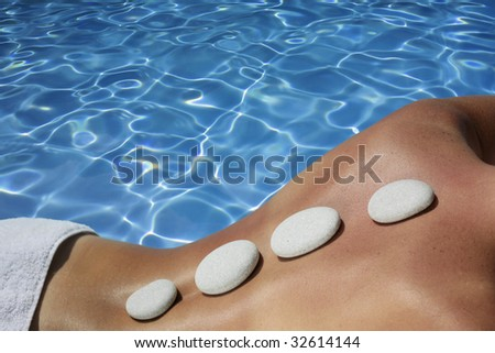 Woman with volcanic massage stones in front of a blue spa pool - stock photo