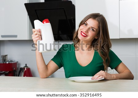Woman with washing detergent and a clean plate - stock photo