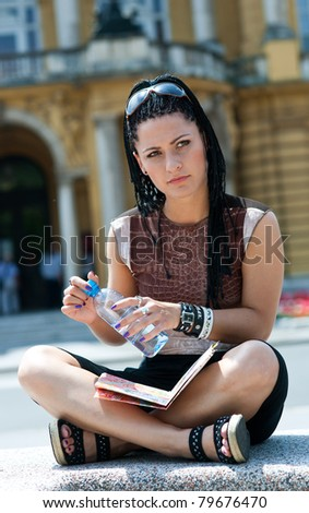 woman with water bottle sitting outside - stock photo