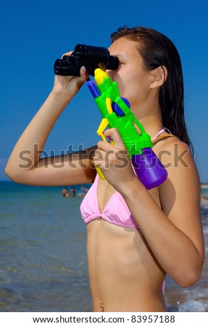 Woman with water-pistol looking through binocular at the beach - stock photo