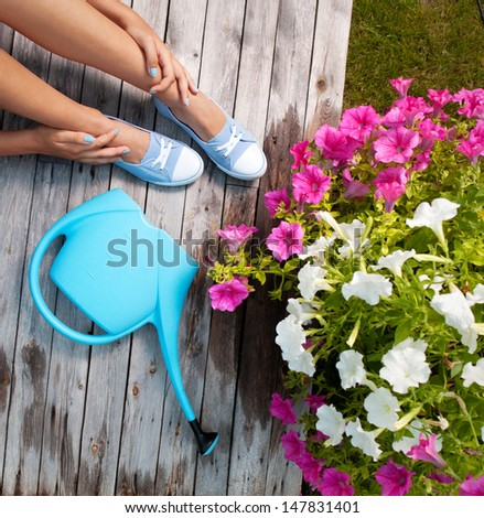 Woman with watering can and flowers on a patio deck - stock photo