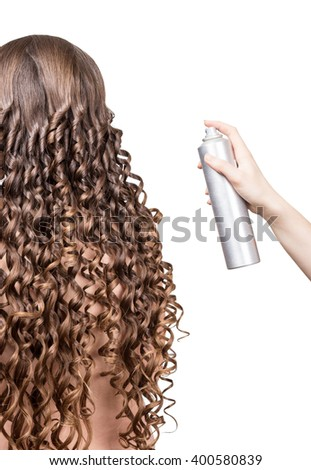 Woman with wavy hair and nail in the hand of the master isolated on white background. - stock photo