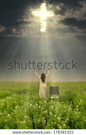 Woman with wheelchair is being healed by God. Shot in meadow - stock photo