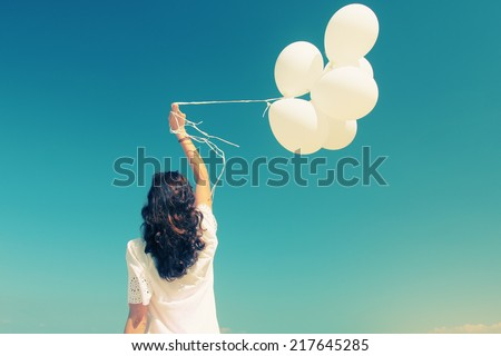 woman with white balloons on seaside - stock photo