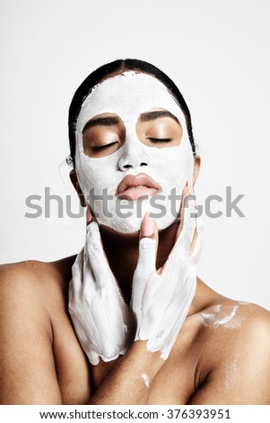 woman with white clay mask on a face and on hands