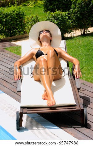 Woman with white hat relaxing by a swimming pool in blue water - stock photo