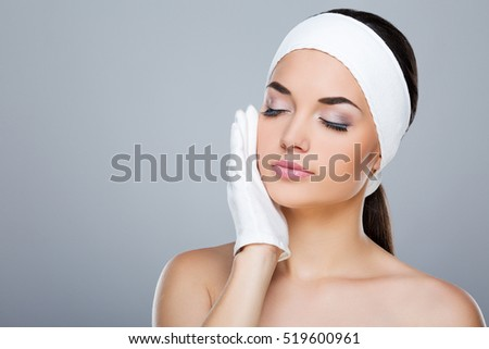 Woman with white headband touching cheek with hand in white glove. Model with closed eyes. Head and shoulders. Beauty salon, studio, indoors, grey background