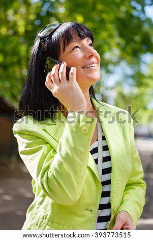 Woman with white smile calling on the smartphone in a street. Happy Lady Dressed in a green jacket and have spring-summer mood