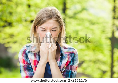 Woman with with allergy symptom blowing nose - stock photo