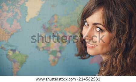 Woman with World Map in Background Looking over Shoulder at Camera as if Planning a Trip - stock photo