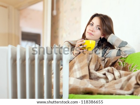 woman  with yellow cup near oil heater at home - stock photo
