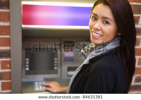 Woman withdrawing cash at an ATM - stock photo