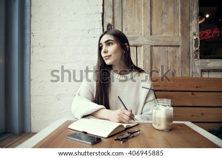 Woman work in cafe, with note pad  in a cafe near window lunch time with coffee - stock photo
