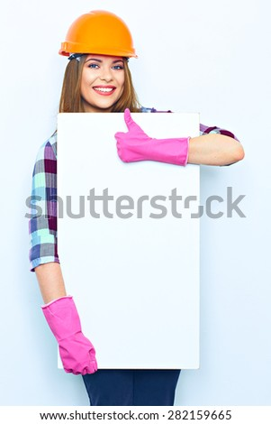 Woman worker builder holding big sign board against show thumb up. Building helmet. Pink glow. - stock photo