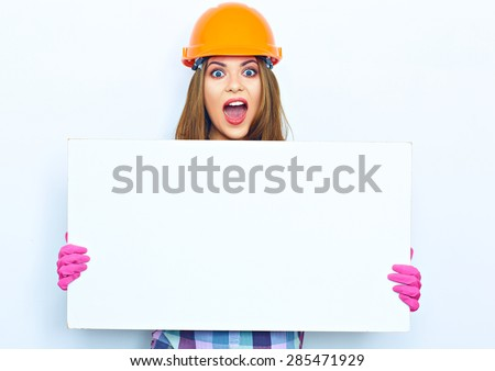 Woman worker builder with open mouth hold big white banner against white background. Building helmet. Pink glow. - stock photo
