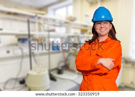 Woman worker in orange overall and blue safety helmet on industrial background