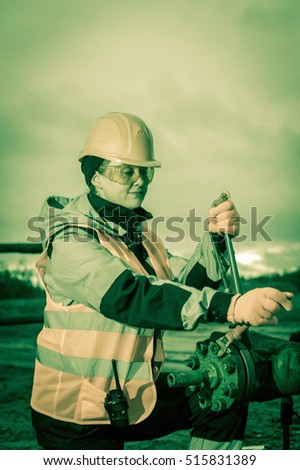 Woman worker on the oil field repairing of oil and gas well, with the wrench wearing  helmet and work clothes. Working process on oil wellhead. Toned.