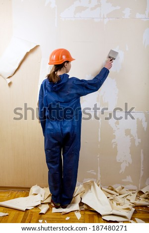 woman worker removes old wallpaper