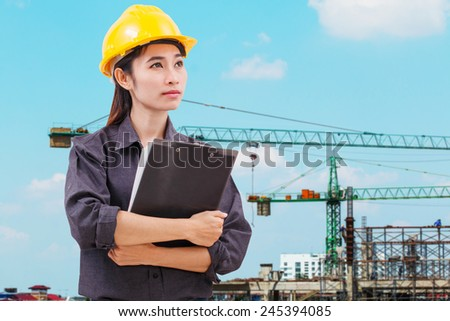 Woman worker with yellow hat on construction background