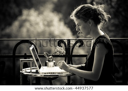 woman workig on a laptop on the balkony - stock photo