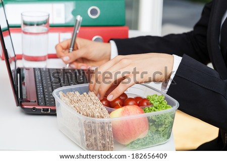 Woman working and eating at office desk - stock photo