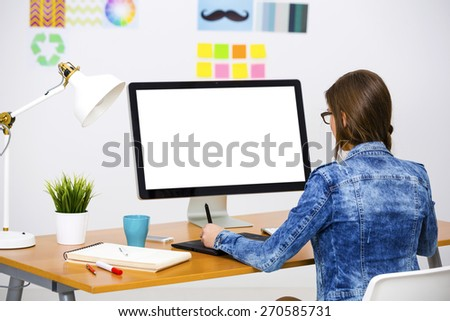 Woman working at desk In a creative office, using a computer  - stock photo
