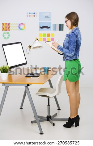 Woman working at desk In a creative office, writting a note  - stock photo