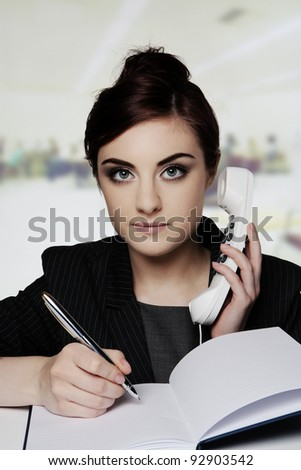 woman working at her desk on her phone - stock photo