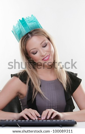 woman working at her desk wearing a christmas hat from a cracker  looking  happy - stock photo