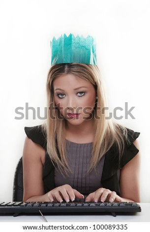 woman working at her desk wearing a christmas hat from a cracker not looking to happy