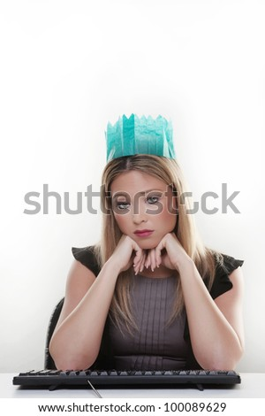 woman working at her desk wearing a christmas hat from a cracker not looking to happy - stock photo