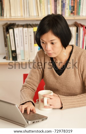 Woman working at home with laptop on desk.