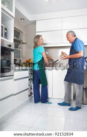 Woman working at kitchen counter while man eating salad - stock photo