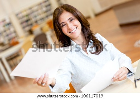 Woman working at the library and handling a paper - stock photo
