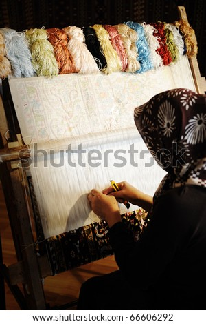 Woman working at the loom. Oriental Muslim national crafts. Focus on the fabric. - stock photo