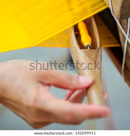 Woman working at  traditional Thai loom at work with spinner - stock photo
