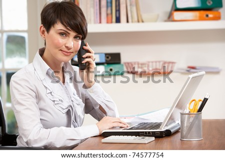 Woman Working From Home Using Laptop On Phone - stock photo