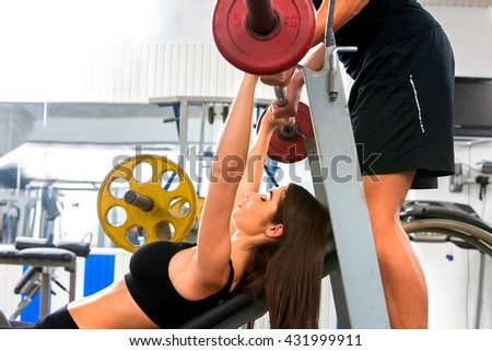 Woman working his arms and chest at gym. She lifting barbell and man back up her barbell in sport gym. - stock photo