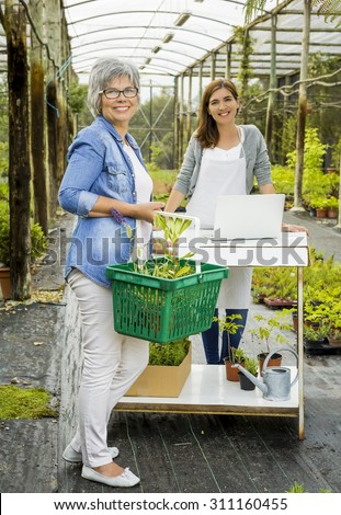 Woman working in a flower shop and talking with a customer - stock photo