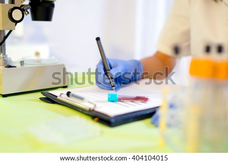Woman working in a laboratory. He writes with a felt pen. Selective focus - stock photo