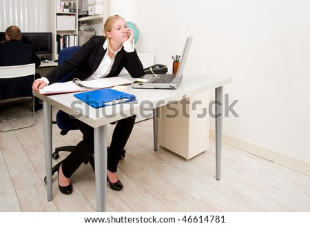 Woman, working in an office, staring blankly at a blind wall out of boredom