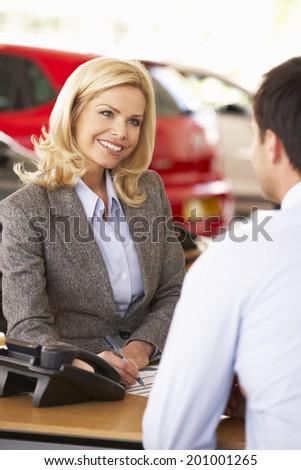 Woman working in car showroom - stock photo