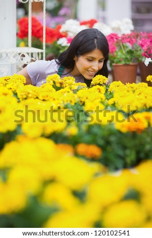 Woman working in garden center smelling yellow flowers - stock photo