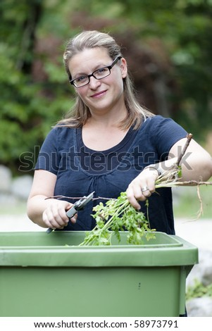 Woman working in her garden preparing for autumn - stock photo