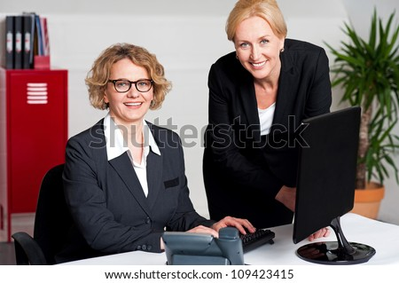 Woman working in office with colleague in front of computer - stock photo