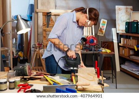 Woman working in workshop, using top handle jigsaw. - stock photo
