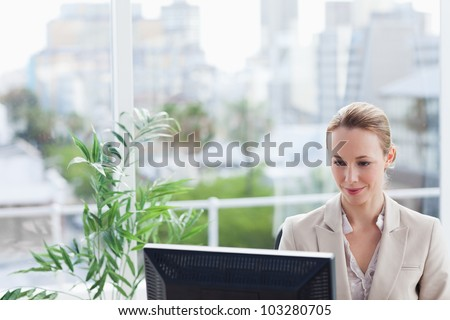 Woman working on a computer with city view in background - stock photo