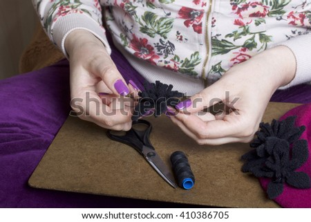 Woman working on a headdress. Cuts flowers from wool fabric. Sewn on the beret. Handmade.