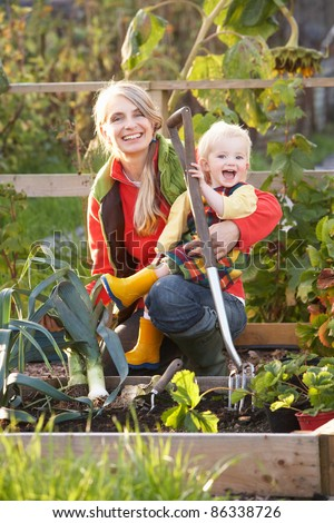 Woman working on allotment with child