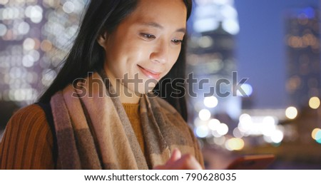 Woman working on cellphone in the city at night